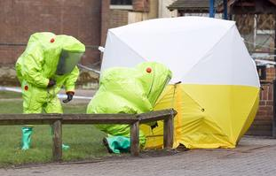 Personnel in hazmat suits  examine the scene where the Skripals were found