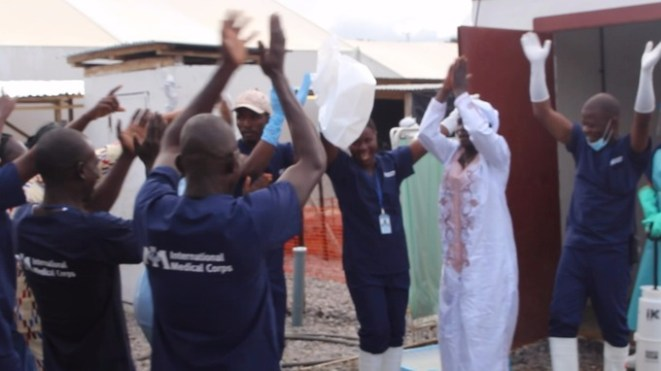 Medical staff cheer as Adama Sankoh, the last confirmed Ebola patient, leaves hospital after treatment