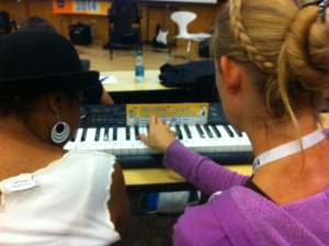 Two teachers share a keyboard and a Jam Card at a Rock Fest 2014 workshop
