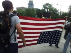 According to Code of Laws of the United States of America holding a flag upside down is a signal of distress which is what the protesters said they were trying to communicate.