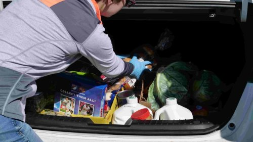 Community Food Share staff member Shana Waldman, Volunteer Coordinator, loads food into a participant's car during the food bank's drive-through pantry on March 18, 2020.
