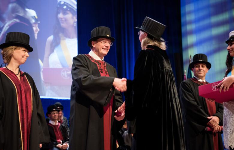Professors in hats and robes, shaking hands at the inauguration ceremony in Aula Medica 2016.