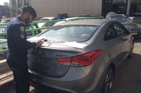 Traffic police remove license plates of cars blocking