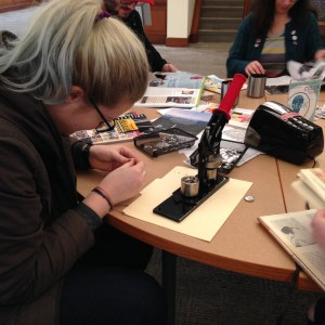 Student creates buttons during Brain Fuel Week at the DePaul Library