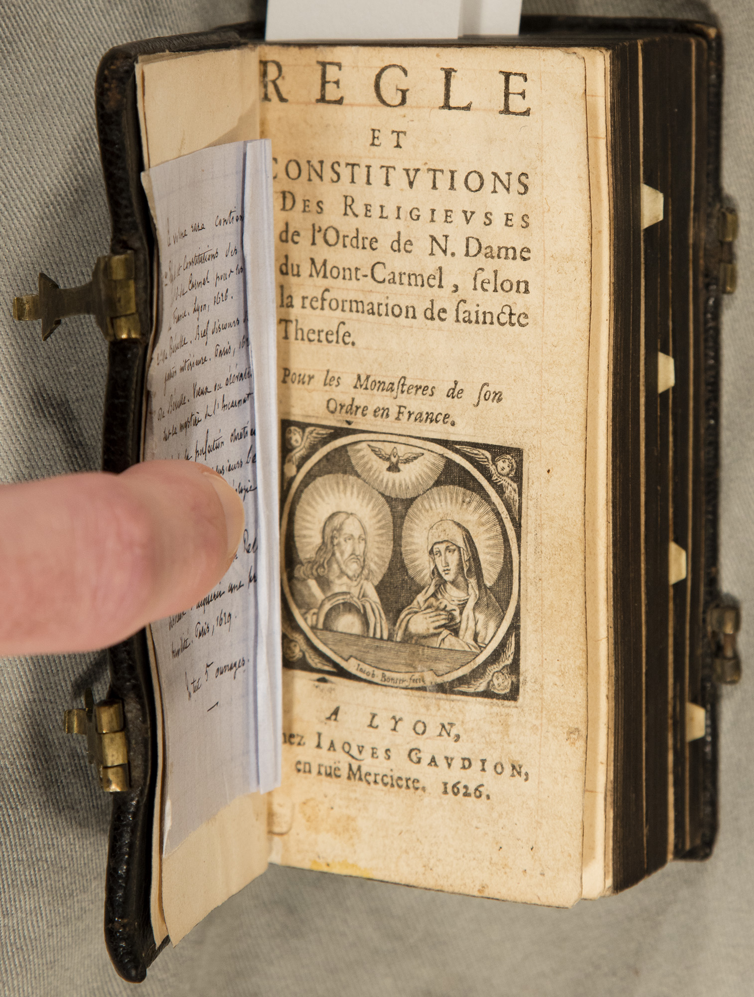 Image showing the title page of Regle et constitutions des Religieuses de l'Ordre de N. Dame du Mont-Carmel, selon la reformation de Saincte Therese: pour les monasteres de son ordre en France, 1626. There is a woodcut of two nuns in prayer.