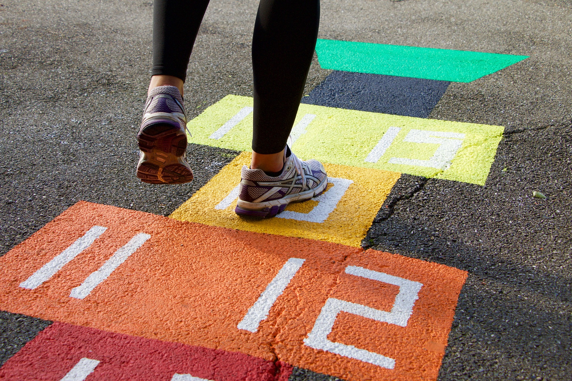 child jumping on a colorful hopscotch court outdoors