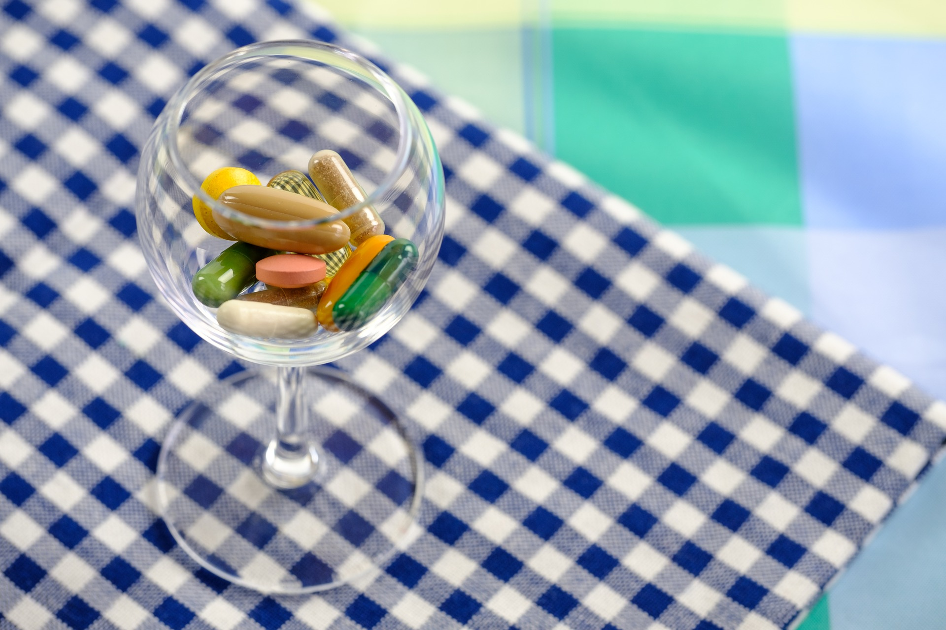 photograph of multicolored vitamins in a glass on a table