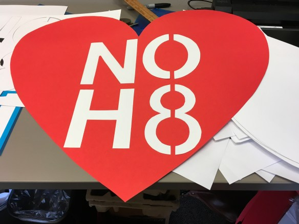 """Anonymous, """"Making signs"""" —a red and white sign in the shape of a heart saying """"No H8"""""""