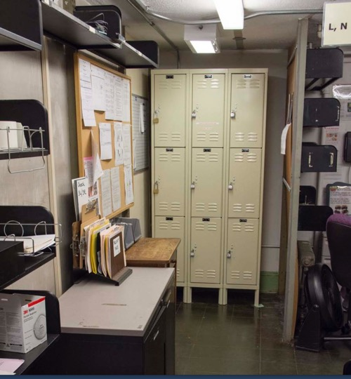 A cramped corner with bulletin boards, inboxes, and old-style lockers