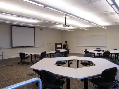 Room with artificial, fluorescent lighting, whiteboards on the walls, tables configured in circles with chairs around them