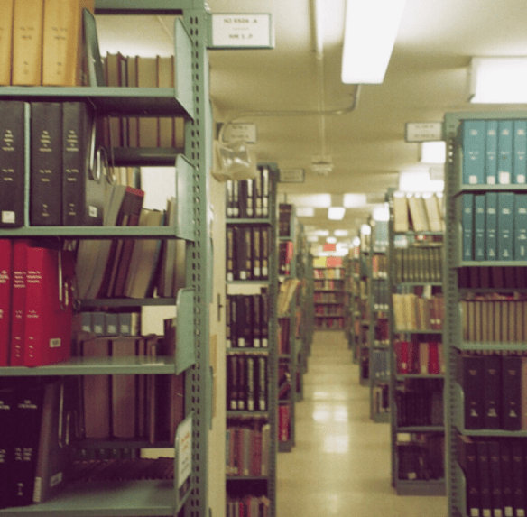 A view down the corridor of book stacks, shelves on either side