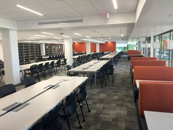 View of tables, chairs near windows on 1st floor of Clemons Library