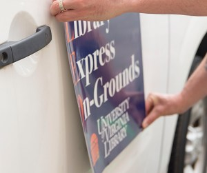 A pair of hands hold a large plastic decal in close proximity to the side of a white vehicle door