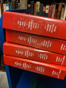Image of books with transparent Braille title labels placed over the titles orginally stamped by the bindery.