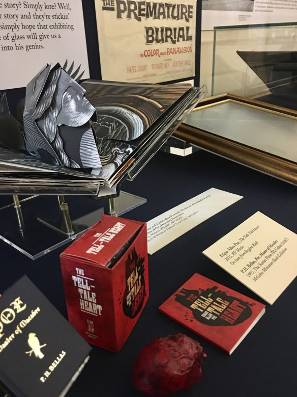 """Display case of Poe items in the exhibition: a pop-up book of Poe's The Raven and miniature book of his story """"The Tell-Tale Heart."""""""