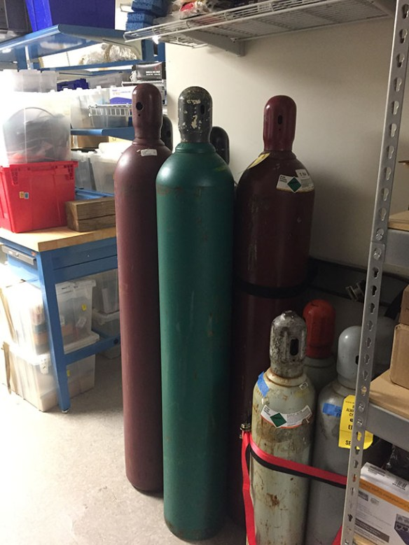 several tall, cylindrical tanks grouped together in a storage area