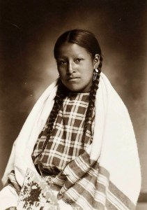 Portrait of a young woman seated, with braided hair and wearing a checked print dress with a striped blanket shawl over her shoulders.