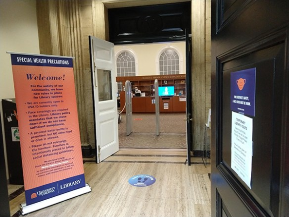 The door to brown library has signage reminding patrons to wear facial coverings and practice social distancing