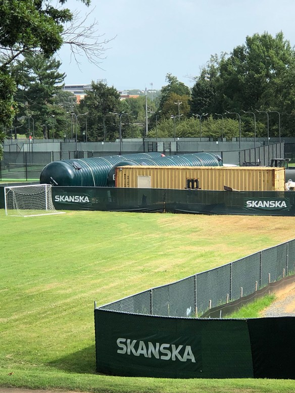 View of the tanks behind a Skanska contractor's fence in Nameless Field with the University Avenue tennis courts in the background