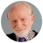 Photo of cartoonist Kal Kallaugher, smiling bearded man wearing colorful shirt and solid tie