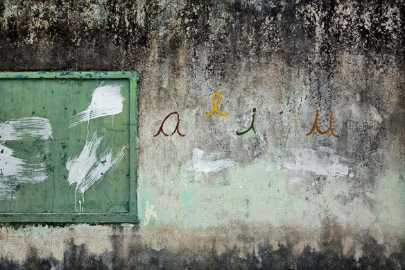 Concrete wall with cursive letters a e i and u painted in colors