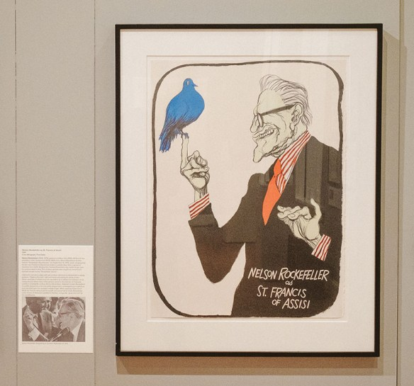Display of depiction of a grinning Nelson Rockefeller in modern dress as St. Francis, extending his middle finger of his right hand upon which a bird perches, and extending the pinky of his left hand. Oliphant's image is displayed next to his inspiration, a news photo of Rockefeller flipping off some hecklers.