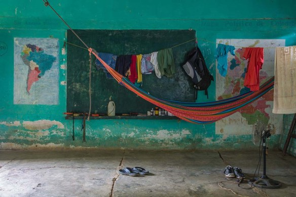 A brightly painted wall with hammock and concrete floor