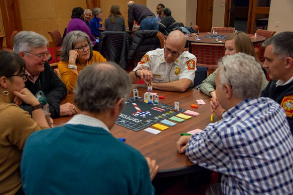 A group of players gathered around the table watching as one moves his avatar on the gameboard.