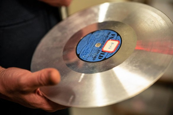 Photo of a grooved aluminum disc with a blue label held in someone's hand.