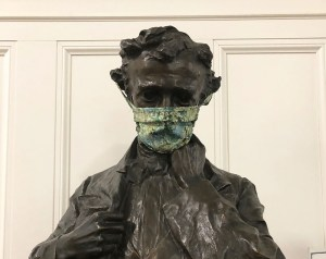 Bust statue of Edgar Allan Poe, in the main library, a cloth medical mask over his mouth and nose.