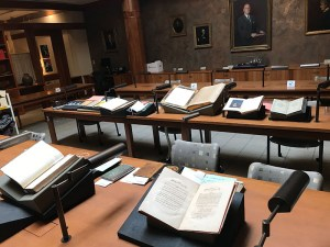 Tables in the Special Collections reading room, lined with books, open on book cradles in preparation for a virtual class.