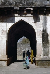 A large, pointed arch enters a shady passageway through a light gray building bathed in bright sunlight, with women, robed in traditional Indian garb, passing through.