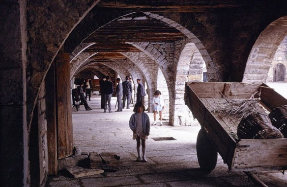 A series of pointed arches leads through a passage. Light from outside comes through a series of arches to the right. In the center of the passage, a female child in a short dress and knee socks stands next to a tilted cart, a couple of large baskets in it.