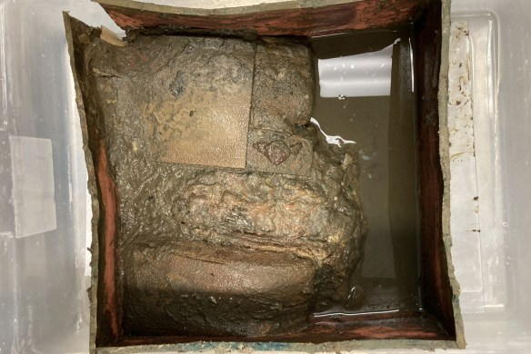 Photo of time capsule and contents as it arrived to the UVA Library's special collections: photo shows copper box from above, split on one end with no lid. Inside the box is a soggy mess of pulpy paper and brown liquid.