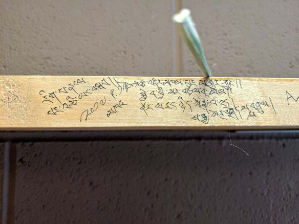 Tibetan text written in ink on the outer edge of a carrel bookshelf.