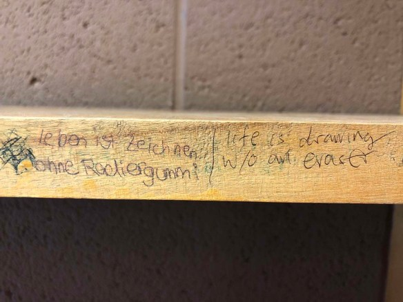"""German text printed in ink on the outer edge of a carrel bookshelf: """"Leben ist zeichnen ohne Radiergummi"""", followed by the English equivalent, """"life is drawing w/o an eraser""""."""