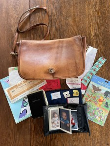 A leather purse with stamps, stickers, notes, and photographs