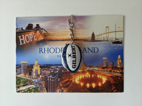 A postcard with a keychain hanging over the top. The keychain is a chain with a small football at the end.