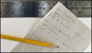 Pencil and ruler with hand-written note showing measurements