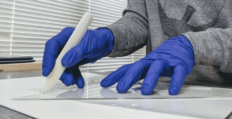 A gloved person uses a bone folder to score a sheet of Mylar