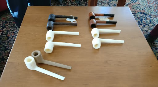 Original pipes with stained and unstained white replicas lined up in two rows on a table top.