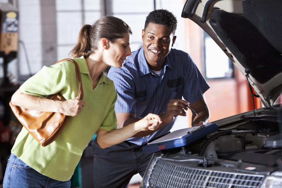 Mechanic and customer looking under the hood of a vehicle