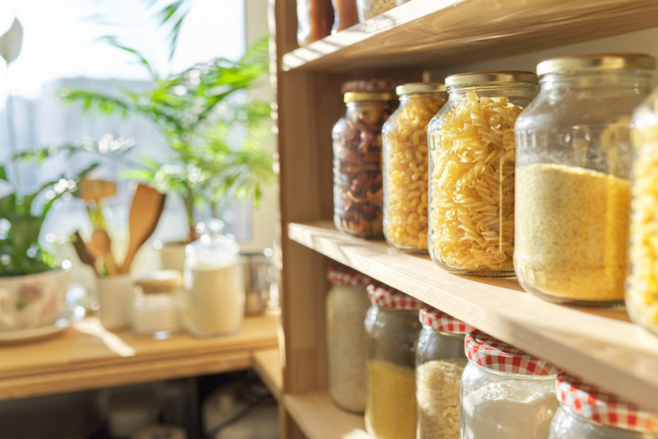 Wooden shelves in pantry for food storage, grain products in storage jars