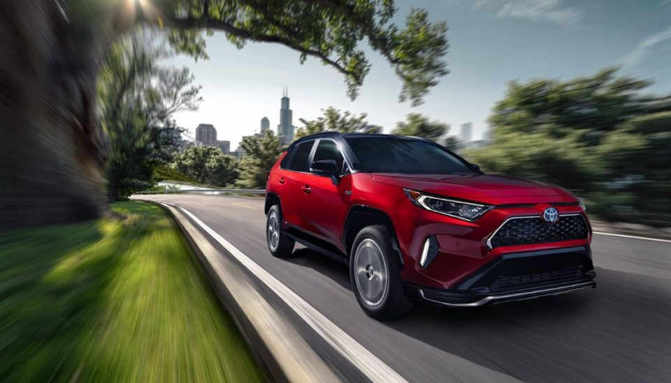 A red 2021 RAV4 driving on the road.