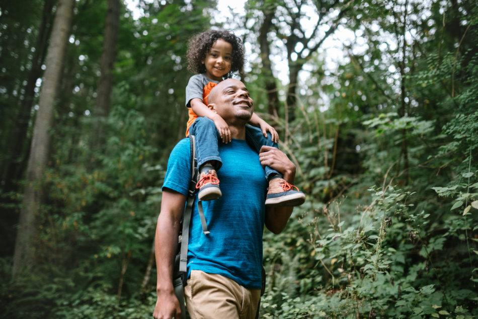 Father carrying son on his shoulders while hiking