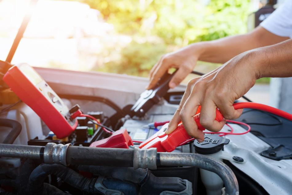 Man jump starting car battery