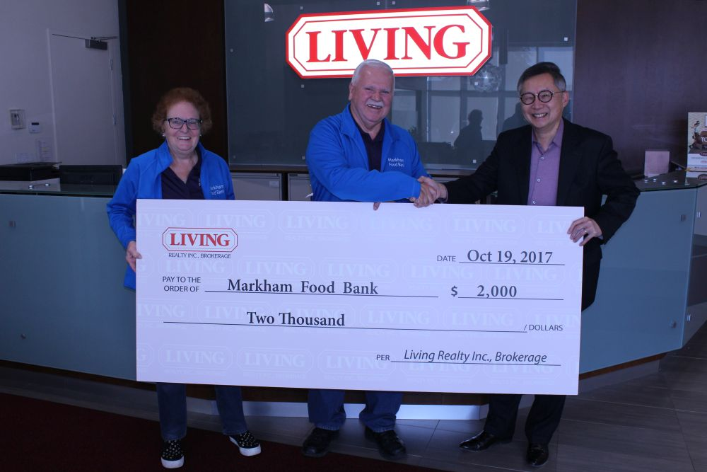 Stephen Wong, president of the Living Group of Companies, hands over a $2000 cheque following a successful food drive
