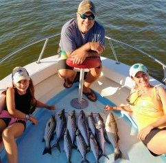 Photo of family on boat with striped bass