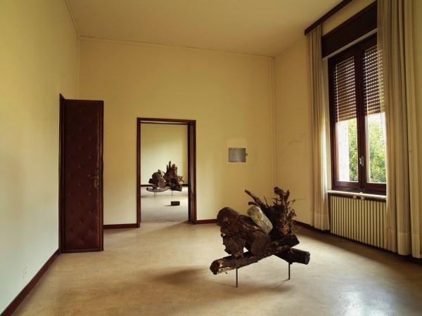 Wooden sculpture in room, another wooden sculpture visible through doorway.