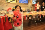 Annie, 5, who declined to give her last name, was showing her mother a two-sided flag she just made. The family moved to Chicago from China two years ago. (Wenjing Yang/MEDILL)